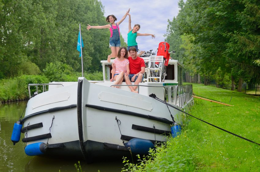 Family vacation, travel on barge boat in canal, happy parents with kids having fun on river cruise in houseboat