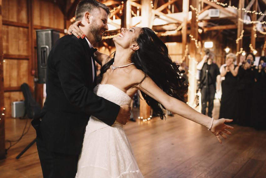 Bride shakes her dark hair while dancing with a groom