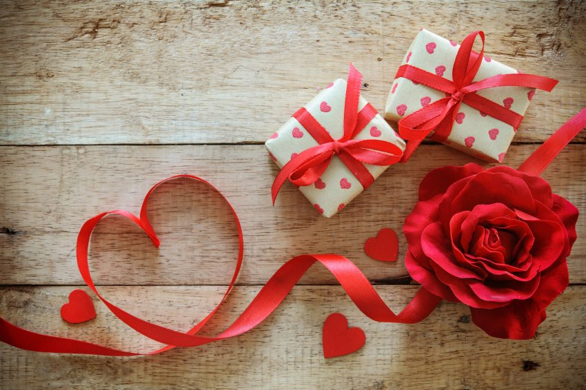 Ribbon shaped heart with a rose and gift boxes for Valentines Day on wooden background