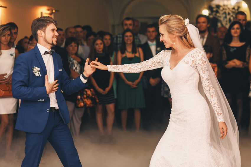 Handsome groom in blue suit takes bride's hand while he dances w