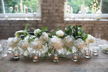 white peonies are in glass bottles next to the candles on vintage wooden table in the loft
