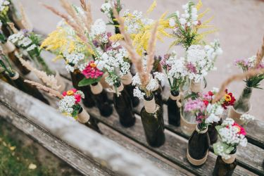 flowers and herbs in glass bottles standing on an old wooden bench in the garden